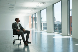 Businessman sitting in chair in empty office space, looking out of windowの写真素材 [FYI03587641]