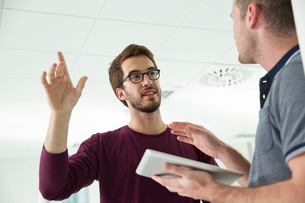 Two men, having conversation, holding digital tabletの写真素材 [FYI03587651]