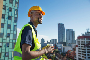 Construction worker outdoors, holding takeaway coffee cup, elevated view of surrounding buildingsの写真素材 [FYI03587669]