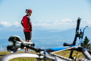 Senior man wearing cycling helmet, standing on hillside, looking at view, bicycle in foregroundの写真素材 [FYI03587714]