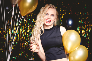Portrait of young woman at party, holding champagne glassの写真素材 [FYI03587807]