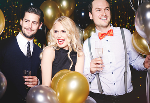 Portrait of three people at party, surrounded by balloons, holding champagne glassesの写真素材 [FYI03587810]