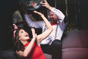 Man and woman fooling around at party, man holding disco ball above woman's headの写真素材 [FYI03587829]