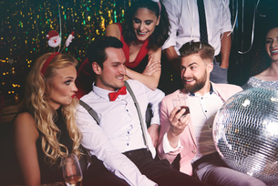 Group of friends sitting together at party, man holding disco ball in lapの写真素材 [FYI03587830]