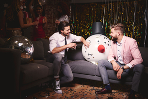 Two men sitting on sofa at party, giant snowman head in-between them, laughingの写真素材 [FYI03587841]
