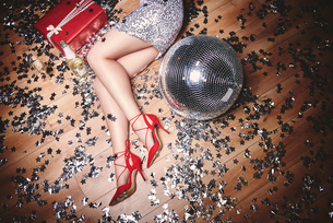 Woman lying on floor at party, surrounded by glitter, champagne bottle and disco ball, overhead viewの写真素材 [FYI03587842]