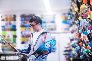 Young male skateboarder looking at skateboards in skateboard shopの写真素材 [FYI03587874]