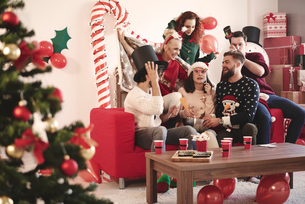 Young adult friends trying on party hats at christmas partyの写真素材 [FYI03587948]