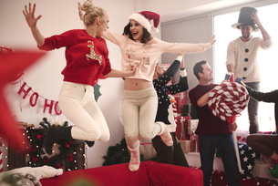 Young women jumping on sofa at christmas partyの写真素材 [FYI03587957]
