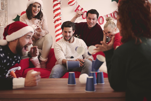Young adult friends throwing ball at paper cups at christmas partyの写真素材 [FYI03587960]