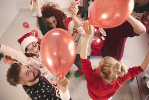 Overhead view of young adult friends dancing with balloons at christmas partyの写真素材 [FYI03587982]