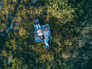 Overhead view of friends lying on blanket on grass, Firenze, Toscana, Italy, Europeの写真素材 [FYI03588045]