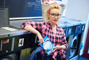 Bored staring woman in laundretteの写真素材 [FYI03588241]