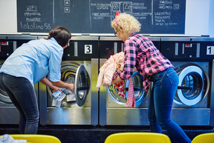 Two women inserting laundry into washing machines at laundretteの写真素材 [FYI03588242]