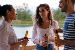 Three friends outdoors, in conversation, holding bottles of beerの写真素材 [FYI03588308]