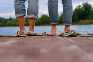 Two women, standing on pier, barefoot, low section, rear viewの写真素材 [FYI03588311]