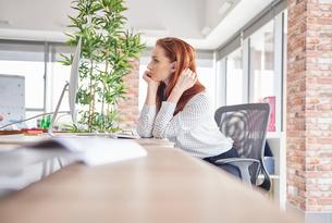 Woman sitting at desk looking awayの写真素材 [FYI03588415]