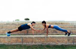 Man and woman exercising outdoors, doing push-ups on steps, South Point Park, Miami Beach, Florida,の写真素材 [FYI03588541]