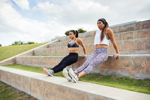 Two young women exercising outdoors, doing push-ups on steps, South Point Park, Miami Beach, Floridaの写真素材 [FYI03588543]