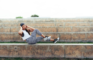 Young woman exercising outdoors, doing sit-ups on step, South Point Park, Miami Beach, Florida, USAの写真素材 [FYI03588566]