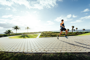Young man exercising, running outdoors, South Point Park, Miami Beach, Florida, USAの写真素材 [FYI03588572]