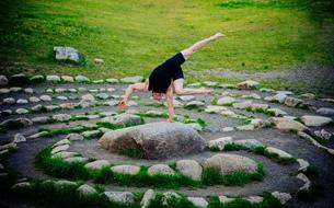 Acrobat performing on stone arrangement, Bainbridge, Washington, USAの写真素材 [FYI03588584]