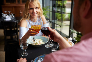 Over shoulder view of couple raising a toast at restaurant tableの写真素材 [FYI03588596]