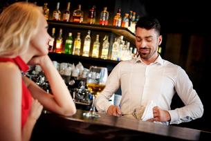 Barman flirting with young woman sitting at barの写真素材 [FYI03588615]