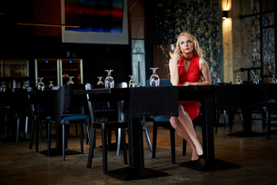 Glamorous young woman with long blond hair sitting alone at restaurant tableの写真素材 [FYI03588621]