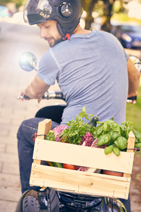 Rear view of man on motorcycling transporting vegetables in crateの写真素材 [FYI03588733]