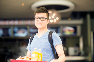 Man holding tray of fast food looking at camera smilingの写真素材 [FYI03588791]