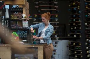 Woman working in skateboard shop, checking wheels on skateboardの写真素材 [FYI03588838]
