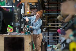 Woman working in skateboard shop, attaching wheels to skateboardの写真素材 [FYI03588840]
