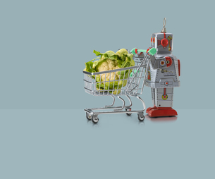 Toy robot pushing miniature shopping trolley with cauliflower against blue backgroundの写真素材 [FYI03588879]