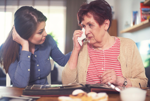 Young woman at table with grandmother crying while looking at photo albumの写真素材 [FYI03588884]