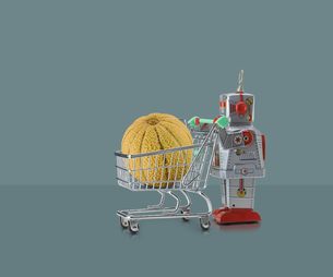 Toy robot pushing miniature shopping trolley with melon against grey backgroundの写真素材 [FYI03588887]