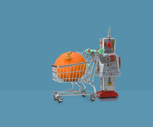 Toy robot pushing miniature shopping trolley with pumpkin against blue backgroundの写真素材 [FYI03588888]