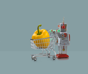 Toy robot pushing miniature shopping trolley with yellow pepper against blue backgroundの写真素材 [FYI03588889]