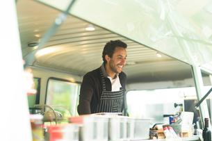 Small business owner preparing food in van food stallの写真素材 [FYI03588901]