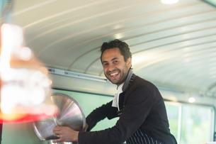 Portrait of small business owner preparing food in van food stallの写真素材 [FYI03588904]