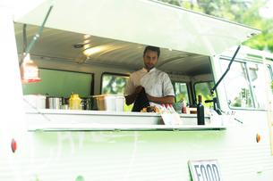 Small business owner preparing food in van food stallの写真素材 [FYI03588908]