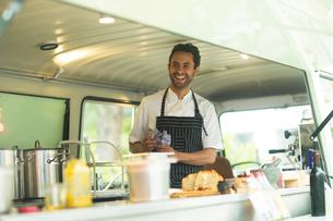 Small business owner preparing food in van food stallの写真素材 [FYI03588909]