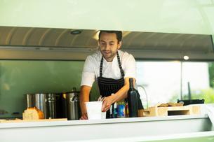 Small business owner preparing food in van food stallの写真素材 [FYI03588912]