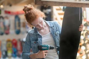 Woman working in skateboard shop, attaching wheels to skateboardの写真素材 [FYI03588930]