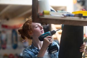 Woman working in skateboard shop, attaching wheels to skateboardの写真素材 [FYI03588935]