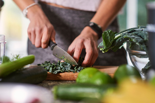 Hands of young woman slicing cabbage at kitchen tableの写真素材 [FYI03588949]
