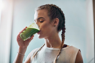 Young woman drinking vegetable smoothie in kitchenの写真素材 [FYI03588953]