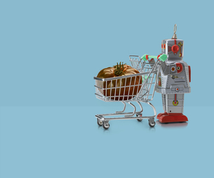 Toy robot pushing miniature shopping trolley with tomato against blue backgroundの写真素材 [FYI03588970]
