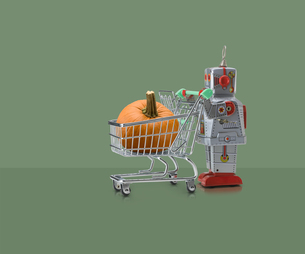 Toy robot pushing miniature shopping trolley with pumpkin against green backgroundの写真素材 [FYI03588971]