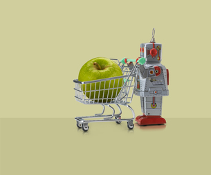 Toy robot pushing miniature shopping trolley with granny smith apple against yellow backgroundの写真素材 [FYI03588975]